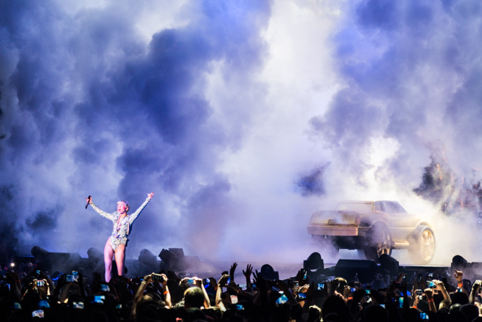 Miley Cyrus, Concert Photos, Vienna, Austria, 2014: Miley Cyrus standing on stage, arms wide apart, fog and golden car