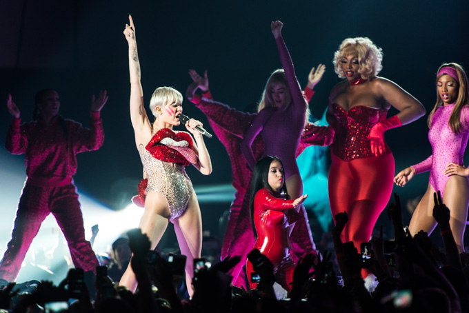 Miley Cyrus, Concert Photos, Vienna, Austria, 2014: Miley Cyrus is dancing on stage and pointing finger to the sky