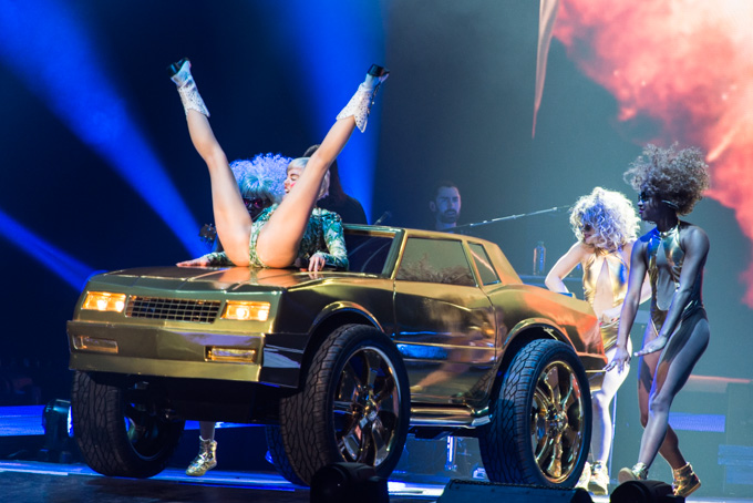 Miley Cyrus, Concert Photos, Vienna, Austria, 2014: Miley Cyrus spreads her legs on the top of a golden car