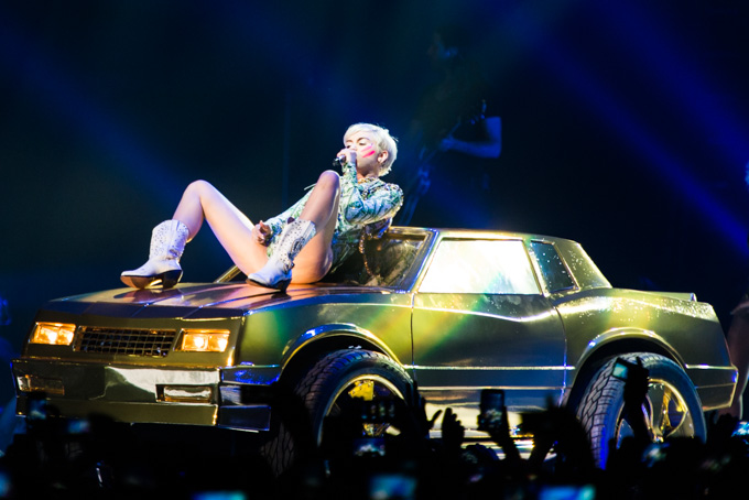 Miley Cyrus, Concert Photos, Vienna, Austria, 2014: Miley Cyrus in a sexy pose on top of a golden car