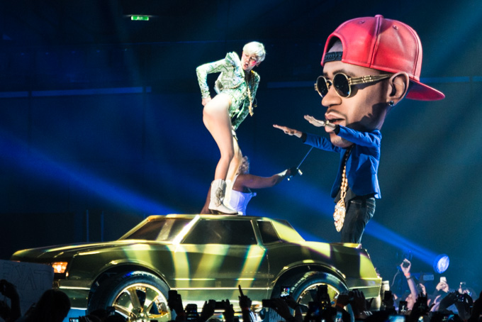 Miley Cyrus, Concert Photos, Vienna, Austria, 2014: Miley Cyrus on top of a golden car, shows her butt and dancing with a big head dancer, red cap