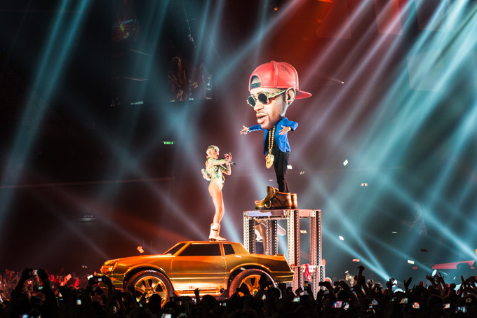 Miley Cyrus, Concert Photos, Vienna, Austria, 2014: Miley Cyrus on top of a golden car dancing with a big head dancer, red cap